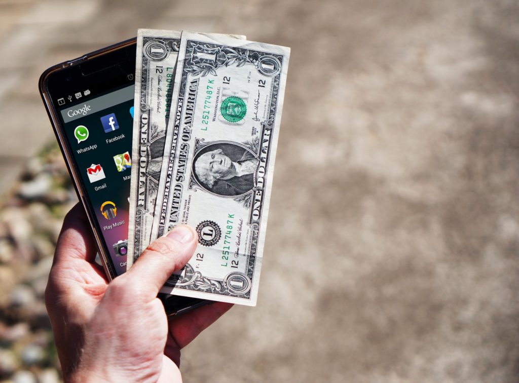 holding phone and money